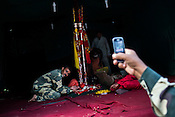 A security officer poses for a photo as his colleagues takes a picture using his mobile phone of the Chari (religious Hindu Stick) at a make shift temple in Chandanwari, the base camp of the journey in Kashmir, India. Hindu pilgrims brave sub zero temperature and high latitude passes and make their pilgrimage to reach the sacred Amarnath cave, which houses a lingam - a stylized phallus, worshiped by Hindus as a symbol of God Shiva. Photo: Sanjit Das/Panos