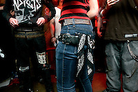 Punk fans link arms and dance together at concert in the basement of the White House in Woodstock, Illinois.  The White House was a small suburban residential home rented by a group of 20-somethings in Woodstock, Illinois, a distant northwestern suburb of Chicago.  For about a year, the renters of the house staged punk-rock concerts in the house's small basement, without the approval of the neighborhood, local government, or police.  .