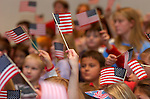 Children hold American flags as they sing patriotic songs during a Veterans Day ceremony to honor local veterans at Montgomery Elementary School.