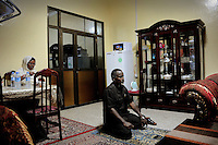Mogadishu/Somalia 2012 -  When returning home for lunch after a hard morning at his office, the Mayor of Mogadishu prays  in his living room while his wife prepares the meal..