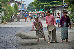 Women spread gravel as they pave a street in Kalay, a town in Myanmar.