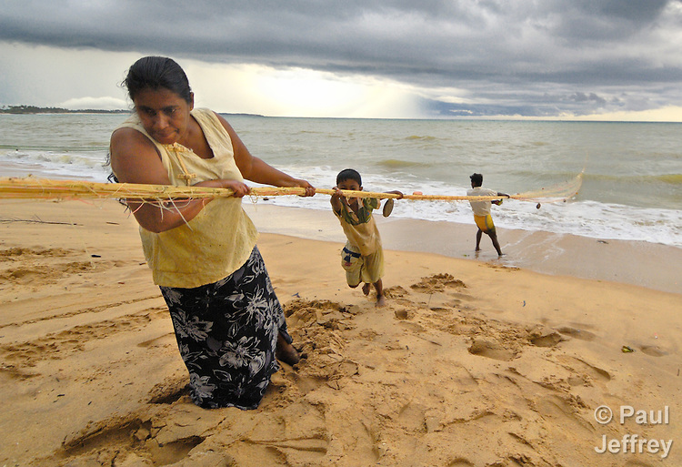 KP Nadlin helps pulls ashore her village's daily catch at Tangalle, on Sri Lanka's southern coast, where the National Christian Council of Sri Lanka, with support from ACT International, has been involved in providing tsunami-affected families with a new start on life. Helping her is six-year old KH Gayashan, and behind him is Premathilaka.