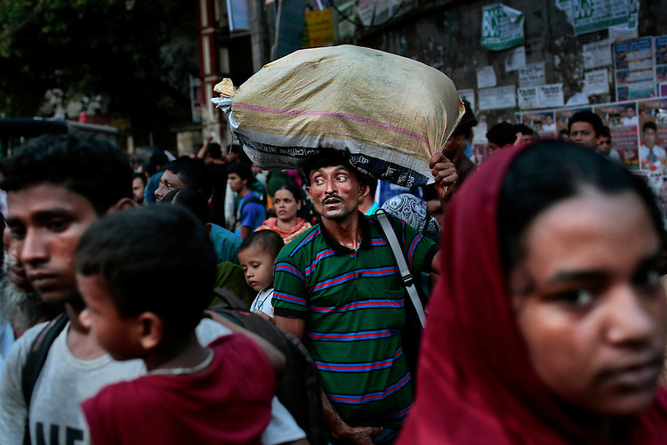 A Bangladeshi man carries a load on his head and walks on a street early morning in Dhaka, Bangladesh.