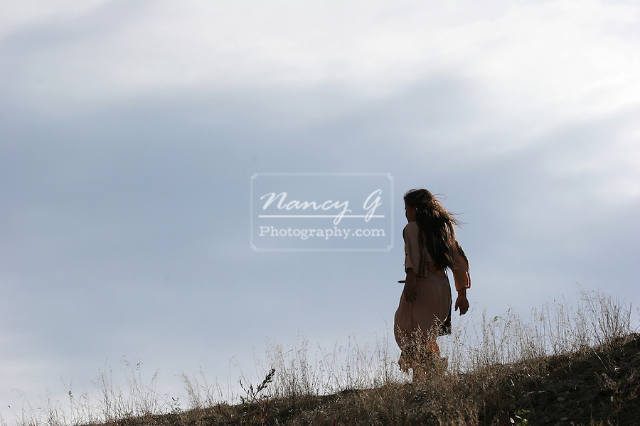 A young Native American Indian child running away in the dried grass