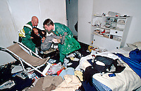Paramedics attending a man found unconscious in a flat. They are lifting him into a wheelchair to enable them to carry him downstairs to the ambulance. There is evidence of drug abuse. The dwelling is used as a refuge for down and outs. This image may only be used to portray the subject in a positive manner..©shoutpictures.com..john@shoutpictures.com