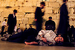 A Jewish man sleeps in front of the Western Wall as others pray or sleep July 18,2002 in Jerusalem's Old City. The Jewish people pray and fast in memory of two Jewish temples destroyed thousands of years ago. As part of the Jewish tradition people spend the night at the Western Wall, the only remain of the second temple, Jews believe, praying or sleeping as a symbol of mourning the destruction. Photo by Quique Kierszenbaum