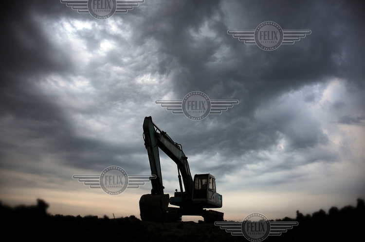 A digger sits poised above the rising mud flow. Since May 2006, more than 10,000 people in the Porong subdistrict of Sidoarjo have been displaced by hot mud flowing from a natural gas well that was being drilled by the oil company Lapindo Brantas. The torrent of mud - up to 125,000 cubic metres per day - continued to flow three years later.