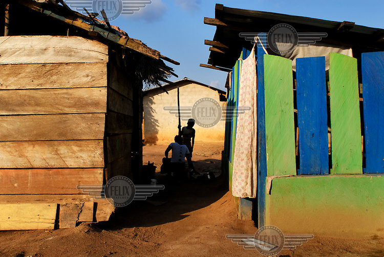 Villagers pound fufu between two houses in the village of Bayerebon 3..