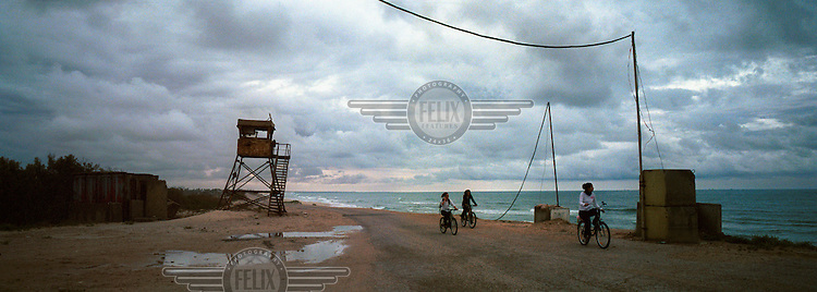 Israeli settlers ride bicycles along the coast, passing an old army outpost. The Israeli government disbanded the settlements in Gaza in August 2005.