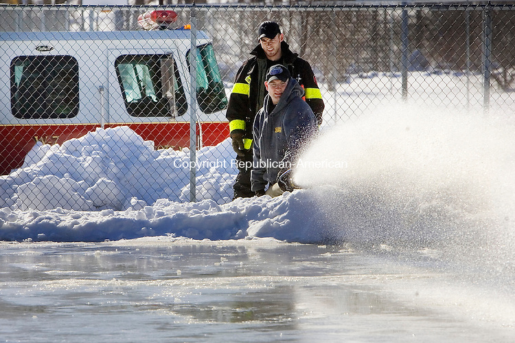 WOLCOTT, CT 16 January 2008-011609SV01--Firefighters Mike Couture Jr. and Jason Kordys spray water on the towns ice rink at Peterson Park in Wolcott Friday.<br /> Steven Valenti Republican-American