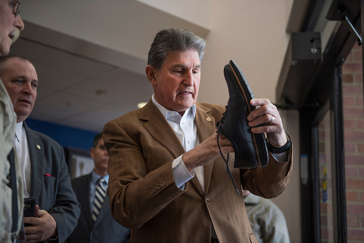 UNITED STATES - MARCH 16: Sen. Joe Manchin, D-W.Va., cleans glass out of his shoe before a town hall meeting at the WVU Robert C. Byrd Health Sciences Center in Martinsburg, W.Va., after his windshield was shattered by a piece of ice, March 16, 2017. Much of the discussion was regarding the American Health Care Act, the Republican's plan to repeal and replace the ACA. (Photo By Tom Williams/CQ Roll Call)