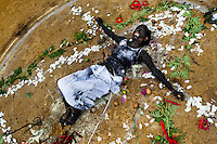 Diana R., who claims to be possessed by spirits, lies on the ground surrounded by flowers after a ritual of exorcism performed by Hermes Cifuentes in La Cumbre, Colombia, 28 May 2012. Exorcism is an ancient religious practice of evicting spirits, generally called demons or evil. Although the formal catholic rite of exorcism is rarely seen and must be only conducted by a designated priest, there are many pastors and preachers in Latin America performing exorcism ceremonies. The 52-year-old Brother Hermes, as the exorcist calls himself, claims to have been carrying out the healing rituals for more than 20 years. Using fire, dirt, candles, flowers, eggs and other natural-based items, in conjunction with Christian religous formulas, he attempts to drive the supposed evil spirit out of a victim's mind and body.