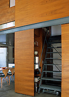 A partially enclosed staircase is tucked between floor-to-ceiling wooden panels with shelves on either side