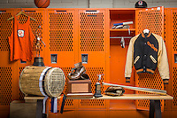 Photo of iconic items from Occidental College's Athletics Department. The Drum, The Shoes, a metal plated baseball bat, Sammy Lee's letterman's jacket, track shoes, a relay race baton, a jersey, goggles, baseball glove, ball and batting helmet and a basketball. Sept. 5, 2012, for the Magazine in the baseball locker room. (Photo by Marc Campos, Occidental College Photographer)