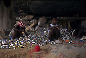 Salvador, Brazil. Poor people sitting under a bridge amongst the tins they have collected to survive.
