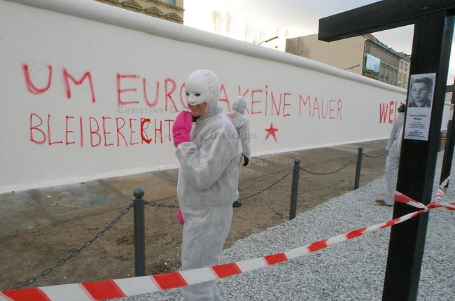 Etwa zwanzig Mitglieder der internationalen  Aktionsgruppe &quot;Kunst gegen Kunst - AG Fluchthilfe&quot; veranstalteten am Sonntag den 19. Dezember 2004 in Berlin am Mauerdenkmal des &quot;Museum am Checkpoint Charlie&quot; auf dem Gelaende des ehemaligen Grenzstreifens in der Friedrichstrasse ein &quot;Happening&quot; unter dem Motto &quot;Von guten und von boesen Mauern&quot;. An der 120 Meter lange Beton Mauer brachten sie die Parolen &quot;Um Europa keine Mauer - Bleiberecht fuer alle&quot; und &quot;Welcome Refugees&quot; an.<br /> Sie wollten mit dieser Aktion an die tausenden von Toten erinnern die an den Aussengrenzen Europas bei der Flucht vor Hunger, Krieg und Armut ums Leben kamen. Auch wollten sie die fragwuerdige Gedenkpolitik kritisieren, die einzig die Toten an der deutsch-deutschen Grenze thematisiert.<br /> Die Gedenkstaette wird privat von Alexandra Hildebrandt, Besitzerin des Museums, betrieben. Das Mauerdenkmal ist, wie die Macherin, in Berlin hoechst umstritten.<br /> 19.12.2004, Berlin<br /> Copyright: Christian-Ditsch.de<br /> [Inhaltsveraendernde Manipulation des Fotos nur nach ausdruecklicher Genehmigung des Fotografen. Vereinbarungen ueber Abtretung von Persoenlichkeitsrechten/Model Release der abgebildeten Person/Personen liegen nicht vor. NO MODEL RELEASE! Nur fuer Redaktionelle Zwecke. Don't publish without copyright Christian-Ditsch.de, Veroeffentlichung nur mit Fotografennennung, sowie gegen Honorar, MwSt. und Beleg. Konto: I N G - D i B a, IBAN DE58500105175400192269, BIC INGDDEFFXXX, Kontakt: post@christian-ditsch.de<br /> Bei der Bearbeitung der Dateiinformationen darf die Urheberkennzeichnung in den EXIF- und  IPTC-Daten nicht entfernt werden, diese sind in digitalen Medien nach &sect;95c UrhG rechtlich geschuetzt. Der Urhebervermerk wird gemaess &sect;13 UrhG verlangt.]