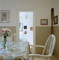 The simply furnished dining room has a floral tablecloth and half-panelled walls