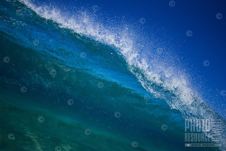 Beautiful blue breaking wave at Makua Beach on the West Side of O'ahu.