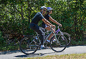 United States President Barack Obama, left, and daughter Malia Obama, right, ride their bicycles on the Manuel F. Correllus State Forest bike path outside of West Tisbury, Massachusetts on Friday, August 15,  2014 during their summer vacation.  They were accompanied by and first lady Michelle Obama (not pictured)<br /> Credit: Rick Friedman / Pool via CNP