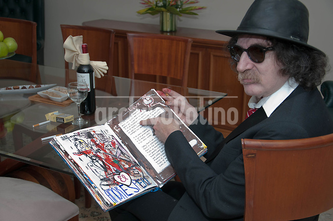 Venezuela: Caracas,13/06/13 <br /> Argentine rock star Charly Garcia, poses in his room at the Hotel Eurobuilding in Caracas, while showing a notebook with sketches and ideas for the suite &quot;Parallel Lines&quot; which will premiere on September 23 at the Teatro Colon, Buenos Aires , Argentina. Garcia was in Caracas, accompanied by his band The Prostitution, giving a couple of concerts of his tour The Unknown Dimension.<br /> Carlos Hernandez/Archivolatino