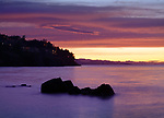 Beautiful dramatic sunset scenery in surreal pink colors on the Pacific ocean coast with lights of residential houses on dark rocky shores in Nanaimo, Vancouver Island, BC, Canada.