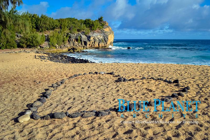 Rock heart on the sand of Shipwreck Beach in Poipu, Kauai, Hawaii, USA