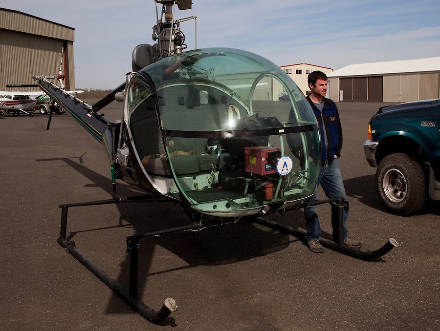A pilot and owner of a small aviation business stands near his Hiller helicopter during the daytime.