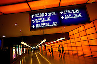 People walk down a colorful hallway in Hong Kong International Airport in Hong Kong.
