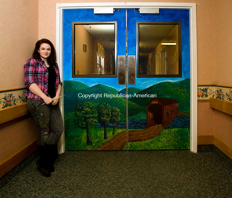"""Torrington-18, January 2010-011810CM01 --Erin McElhone a senior at Torrington High School stands proudly by her finished masterpiece.  The scenic mural took approximately 10-15 hours and is displayed in the locked down dementia unit inside Paradigm Health Center in Torrington.  """"It's [mural] definitely a good experience.  It taught me a lot"""", said McElhone. Victor Leger the art teacher at Torrington High School who oversaw the project describes McElhone as a terrific student and the first person he thought of for the project. Christopher Massa Republican-American"""