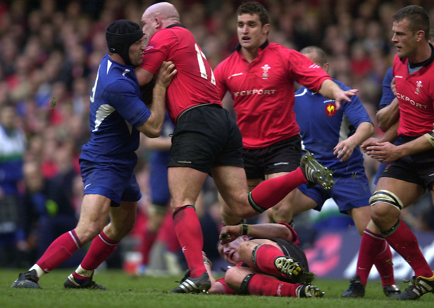 Photo. © Peter Spurrier/Richard Lane Photography.07/03/2004 Six Nations Rugby - Wales v France.Olivier Magne [left] holds up Ben Evans's charge....