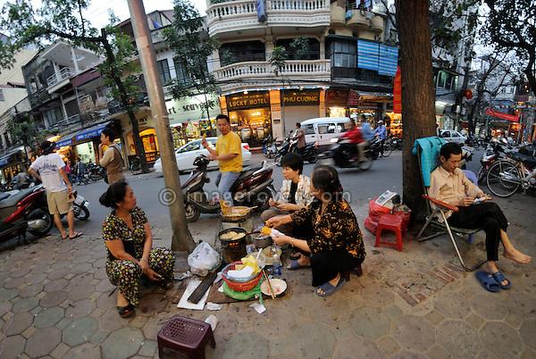 Asia, Vietnam, Hanoi. Hanoi old quarter. Stret vendor selling snacks.