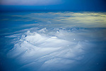 Snow-covered sea ice stretches to the horizon in the Bering Sea in springtime.