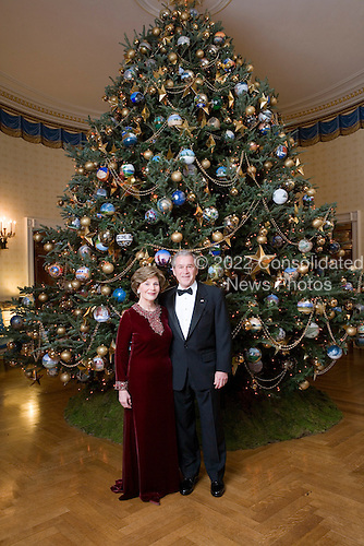 Celebrating the 2007 holiday season, President George W. Bush and Mrs. Laura Bush stand for a portrait in front of the Christmas tree in the Blue Room of the White House.  White House photo by Eric Draper
