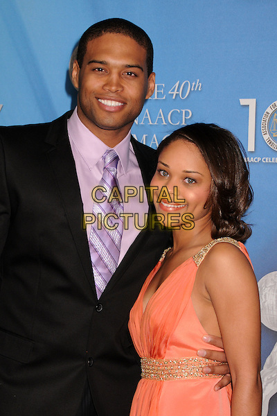 TEXAS BATTLE & GUEST.40th Annual NAACP Image Awards - Arrivals at the Shrine Auditorium, Los Angeles, California, USA..February 12th, 2009.half length black suit jacket peach orange dress purple tie.CAP/ADM/BP.©Byron Purvis/AdMedia/Capital Pictures.