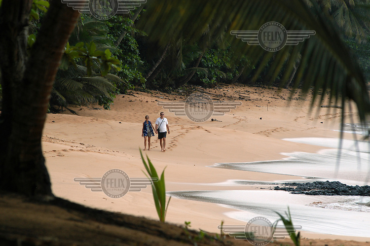 A tourist couple walk hand in hand on the beach at Jale Ecolodge.