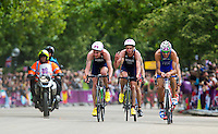 07 AUG 2012 - LONDON, GBR - Alistair Brownlee (GBR) of Great Britain (centre of image, in dark blue) leads the front pack during the bike at the men's London 2012 Olympic Games Triathlon in Hyde Park, London, Great Britain as his brother Jonathan Brownlee (second from right), also racing for Great Britain, discovers he has a time penalty for mounting his bike to soon .(PHOTO (C) 2012 NIGEL FARROW)
