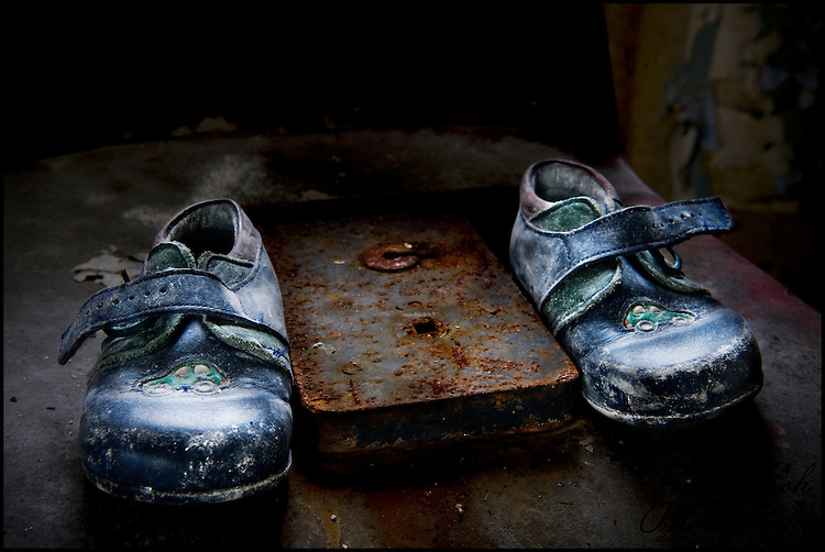 A pair of very small child's shoes with a rusty lock.