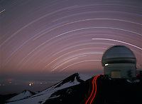 Str trails behind the Gemini North Telescope.  A faint red glow from the eruption of Kilauea volcano can be seen in the lower left.  Mauna Kea, Hawaii.