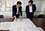 Hidemi Onodera (L), head of the Ishinomaki branch of Japan Post Service Co., Ltd. and ToshiyaFujiwara, manager of the Operations Planning Office at the branch look through plans of the company's coverage area in Ishinomaki, Miyagi Prefecture, Japan on Tuesday 24 May 2011. Almost 100 post office buildings were completely destroyed during  the March 11 magnitude 9 quake and tsunamis that hit northeastern Japan, with 7 out of the 15 buildings operated by the Ishinomaki office being wiped out..Photographer: Robert Gilhooly