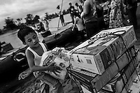 A Guatemalan boy carries smuggled corn flakes and toilet papers on the shore of the Suchiate river in Tecún Umán, Guatemala, 22 May 2011. Having no migration or commercial controls, the Suchiate river serves as an illegal crossing point between the southern Mexican state of Chiapas and Guatemala. Every day, hundreds of people from both countries, crossing the river on the unstable rafts called ?camaras?, smuggle soft drinks, toilet papers, fruits, vegetables and other supplies. The river crossing is also widely used by the Central America immigrants heading to the north, to the United States, in the search of better life.