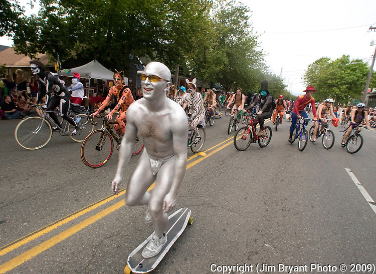 A silver painted parade participant skateboards his way down the street in the 21st annual Summer Solstice Parade held Saturday, June 20, 2009 in Seattle, Wa.The parade was held Saturday, bringing out painted and naked bicyclists, bands, belly dancers and floats. (Jim Bryant Photo © 2009)