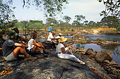 Lukulu, Zambia, Africa. Group of tourists on safari resting in the shade of some trees beside a river.