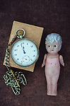 Soiled and punctured vintage celluloid naked girl doll with silver painted hair and worried expression lying on scuffed leather next to pocket watch and chain stating 1158