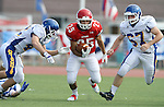 SIOUX FALLS, SD - SEPTEMBER 7:  Caden Quintanilla #25 from Lincoln breaks through Isaac Althoff #42 and Sam Weisensee #67 from O'Gorman in the first quarter of their game at the 2013 Presidents Bowl at Howard Wood Field. (Photo by Dave Eggen/Inertia)
