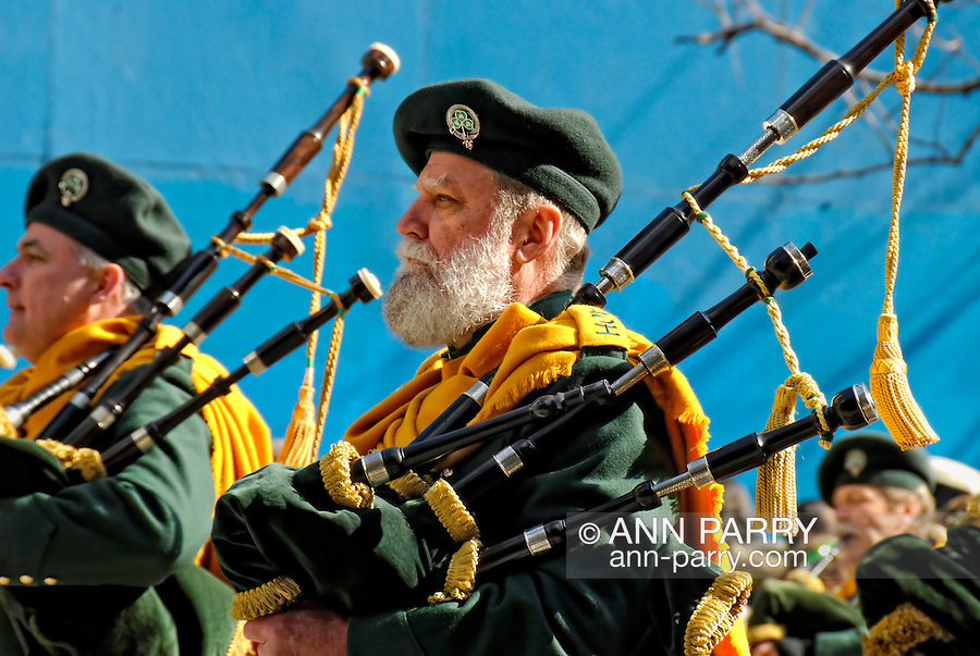 MARCH 17, 2009 - MANHATTAN: Bagpipers, dignified and solemn, in Emerald Society, marching in St. Patrick's Day Parade up 5th Avenue, New York City, NY, USA. Gold tassels hanging from bagpipes, and blue onstruction barrier wall in background. (EDITORIAL USE ONLY)