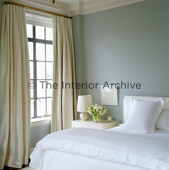 A delicate blue-grey tone for the bedroom wall makes for a calm and restful atmosphere