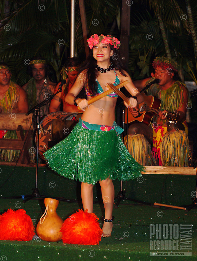 A Hawaiian girl wearing a faux grass skirt and head lei performs with pu'ili, or bamboo sticks, used to enhance rhythm in hula.