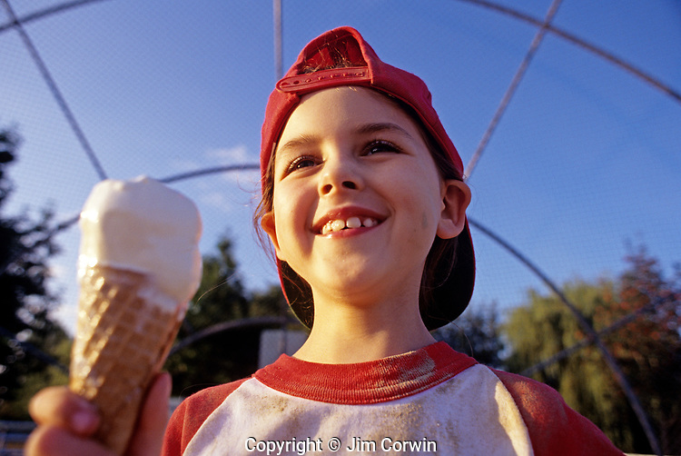 Young girl (7 years old), Little League Baseball player, eating ice cream after game, sunset light, portrait, Woodinville, Washington USA