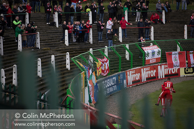 Away supporters and players celebrating their team's opening goal during the first-half action at The Oval, Belfast as Glentoran (in green) host city-rivals Cliftonville in an NIFL Premiership match. Glentoran, formed in 1892, have been based at The Oval since their formation and are historically one of Northern Ireland's 'big two' football clubs. They had an unprecendentally bad start to the 2016-17 league campaign, but came from behind to win this fixture 2-1, watched by a crowd of 1872.