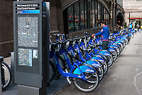 A man uses the Citi Bike NYC bike sharing program by checking out a bicycle from one of the docking stations near Grand Central Terminal.